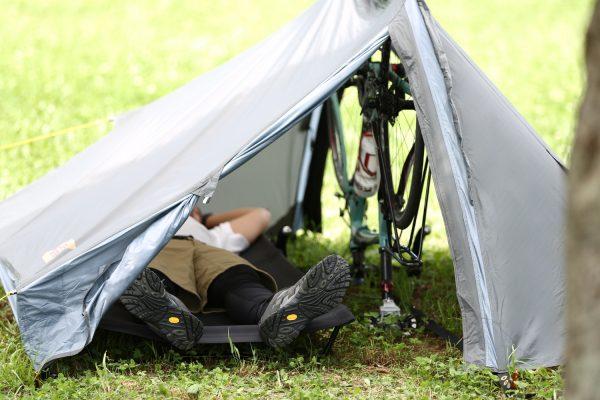 ロードバイク・自転車をポール代わりに設営したテント内のコットでくつろぐバイクパッキングの男性