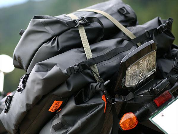 キャンプツーリングなどで多くの荷物をバイクに重ねて積載しているイメージ画像